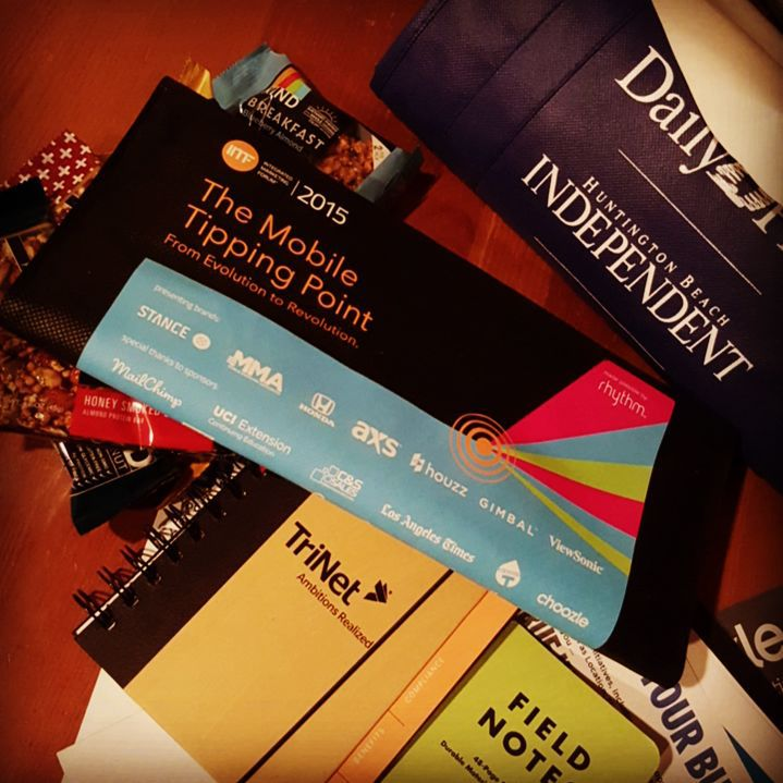 """Inspecting the loot from #2015IMF. #swag #list - Field Notes memo book by vitamin T - Spiral hard bound notebook by Trinet - An obscene amount of KIND bars including their new breakfast bars. - Looks like a deck of cards by @Mailchimp - Postcard about HR and fitness by... Trinet - Mission statement flyer about MMA (Mobile Marketing Association) by... guess who? (Really guys?) - Innovate and grow paper about something or other... TL:DR By... Trinet. (Seriously?) - Postcard about choozle... by choozle -UCI extension continuing education brochure with 20% off by using #coupon """"IMF20"""" at extension.uci.edu - A human head-sized sticker of a creepy lemonhead winking at me. - An awesome sketchpad. It says: 80# Mohawk Everyday Digital Text. By allura, high quality on-demand printing  Comments... Pretty standard bag. The highlights... KIND bars, sketch pad, playing cards. Awesome event by Rhythm Agency.  Disappointed with the lack of creativity and innovation by a couple of the sponsors.  We are at a #marketing conference, by marketers, for #marketers. The hardest demographic to sell to... and you're telling me than an overwritten flyer with your logo is the best you can do to get our attention?  Really?  Those couple sponsors... Wowed me, today, you did not. I hope you took lessons from the speakers and the panel.  Separate blogpost about the terrific event, and people coming up next."""