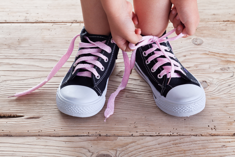 Kid tying pink shoelaces