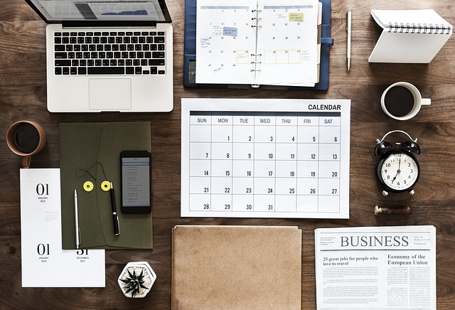 Top view of a desk highlighting a desktop calendar and agenda, as well as a clock and a laptop. Other standard items for a desk are neatly set nearby.