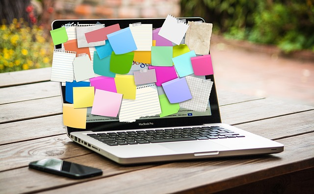 Image of a laptop covered with a huge mess of post it notes. The screen of the laptop is fully covered.