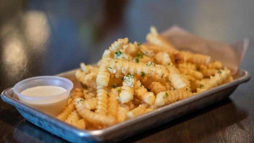 Crinkle-cut fries with garlic sprinkled on top.