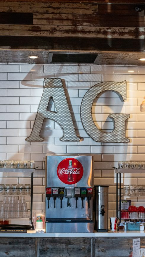 "Photo of the initials ""AG"" for American Grub the letters are hanging over the soda machine."